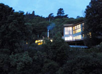 Architect designed bach nestled in the hill surrounded by trees. Large floor to ceiling windows. Evening view.