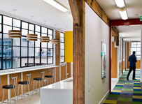 Bright airy heritage building refurbishment with modern interior. Original structure exposed and celebrated against modern elements. Bright primary coloured interior with natural materials.