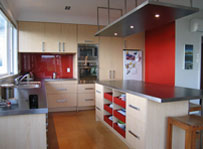 Architect designed modern kitchen. Cork floor tiles light timber cupboards with thick square handles. Central kitchen island with bar stools. Bold red feature walls and splash back. Stainless steel appliances and bench tops. Suspended kitchen island canop